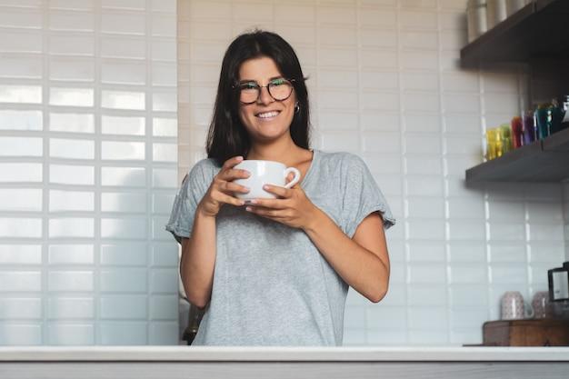 Jeune femme buvant du café à la maison