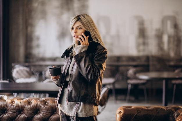 Jeune femme buvant du café et parlant au téléphone dans un café