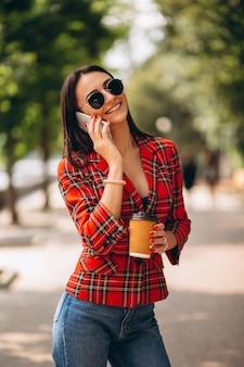 Jeune femme buvant du café et parlant au téléphone