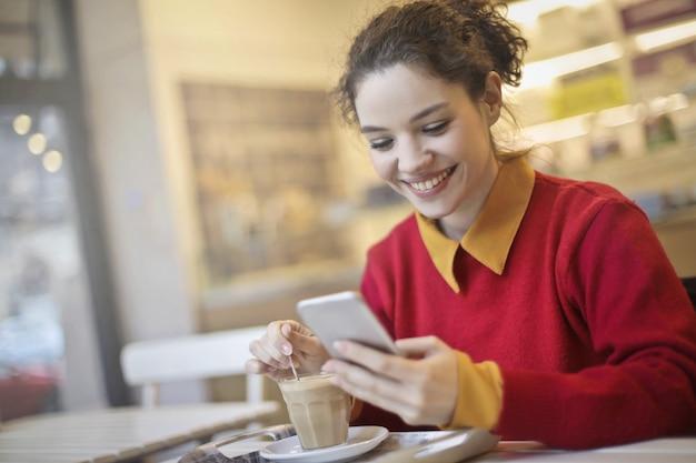 Jeune femme buvant du café et vérifiant son téléphone