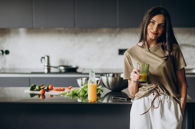 Jeune femme buvant du jus à la maison