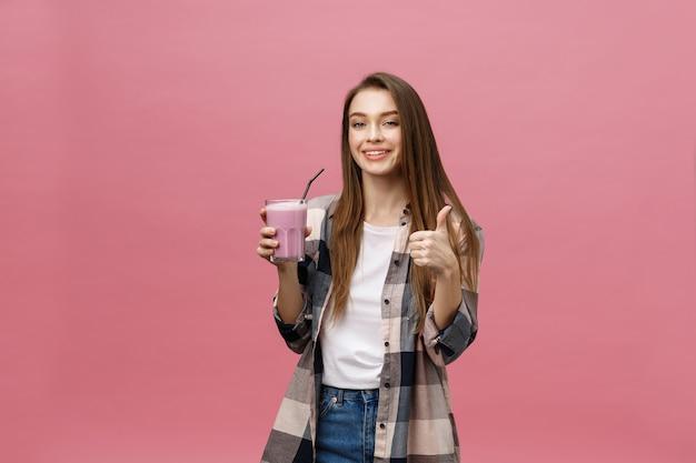 Jeune femme buvant du jus de smoothie avec de la paille