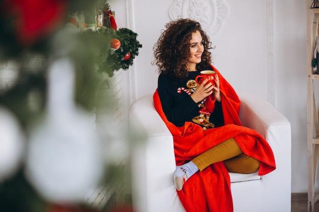 Jeune femme buvant du thé près d'un arbre de noël