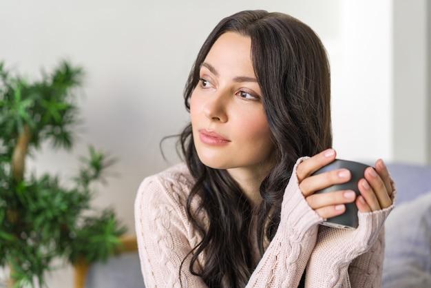 Jeune femme buvant du thé et rêvant assis sur le canapé dans l'appartement lumineux.