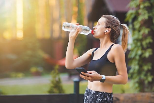 Jeune femme buvant de l'eau après avoir couru et à l'aide d'un téléphone intelligent sur le mur du parc verdoyant.
