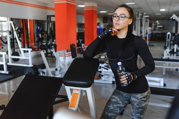Jeune femme buvant de l'eau après l'exercice. salle de fitness.