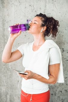 Jeune femme buvant de l'eau et écouter de la musique sur smartphone