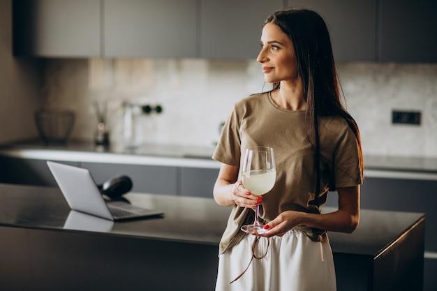 Jeune femme buvant de la limonade de verre à la cuisine