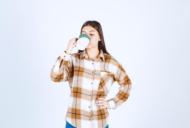 Jeune femme buvant une tasse de café sur un mur blanc.