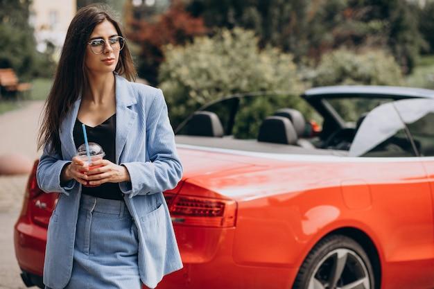Jeune femme buvant un verre de glace à l'extérieur de la rue