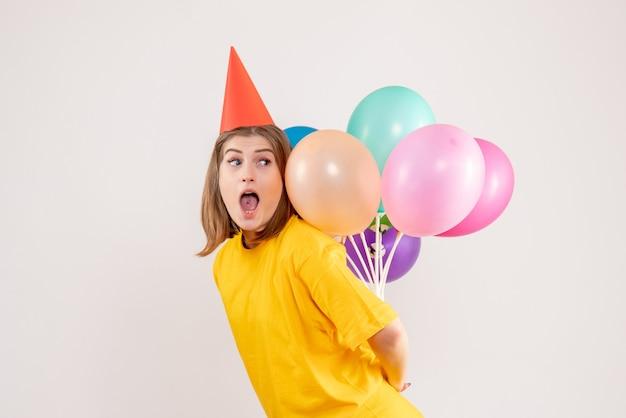 Jeune femme cachant des ballons colorés sur blanc