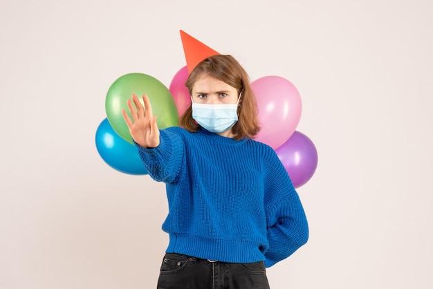 Jeune femme cachant des ballons colorés derrière son dos en masque sur blanc