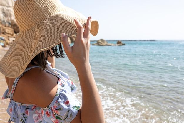 Une jeune femme cache son visage du soleil sous un grand chapeau au bord de la mer.