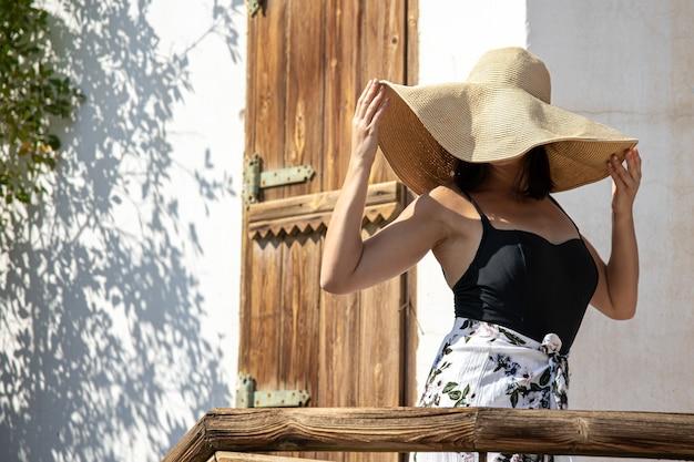Jeune femme cache son visage des rayons du soleil sous un grand chapeau de paille