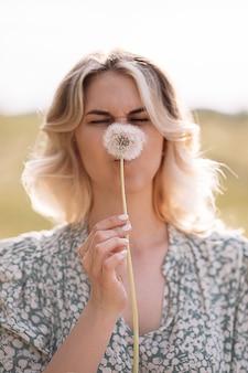 Jeune femme cachée derrière un pissenlit et grimaça drôle. photo drôle. concept d'allergie au pollen