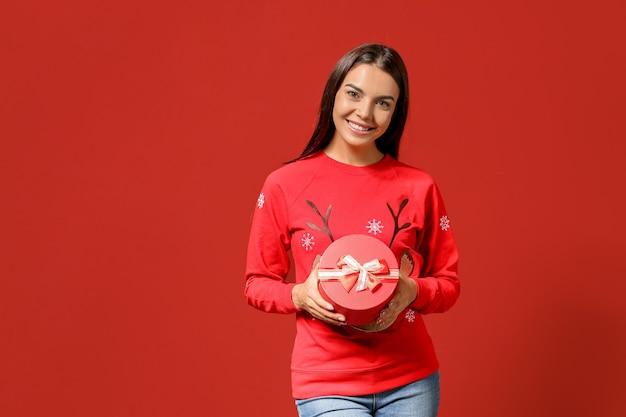 Jeune femme avec un cadeau de noël sur la couleur