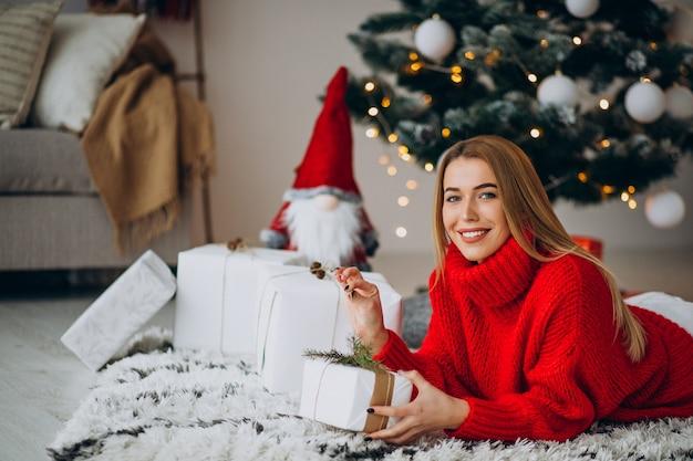 Jeune femme avec des cadeaux de noël par l'arbre de noël