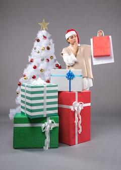 Jeune femme avec des cadeaux de vacances sur gris