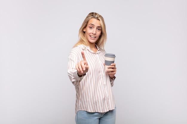 Jeune femme avec un café souriant fièrement et en toute confiance faisant le numéro un pose triomphalement, se sentant comme un leader