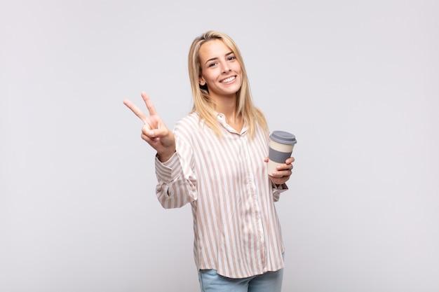 Jeune Femme Avec Un Café Souriant Et à La Recherche De Bonheur, Insouciant Et Positif, Gesticulant La Victoire Ou La Paix D'une Seule Main Photo Premium