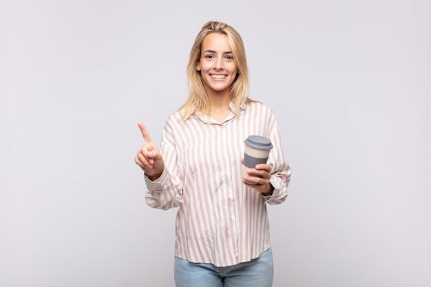 Jeune femme avec un café souriant et à la sympathique, montrant le numéro un ou d'abord avec la main en avant, compte à rebours