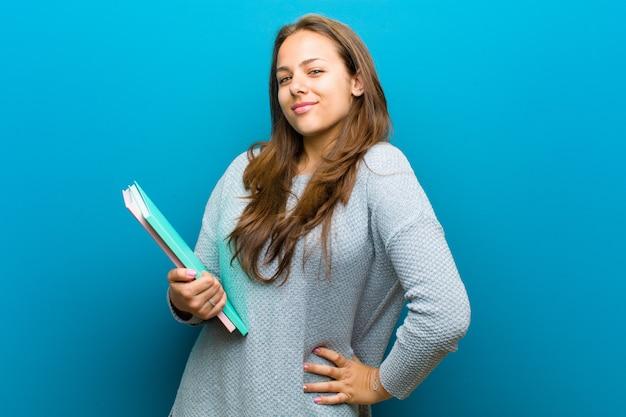 Jeune femme avec un cahier sur fond bleu