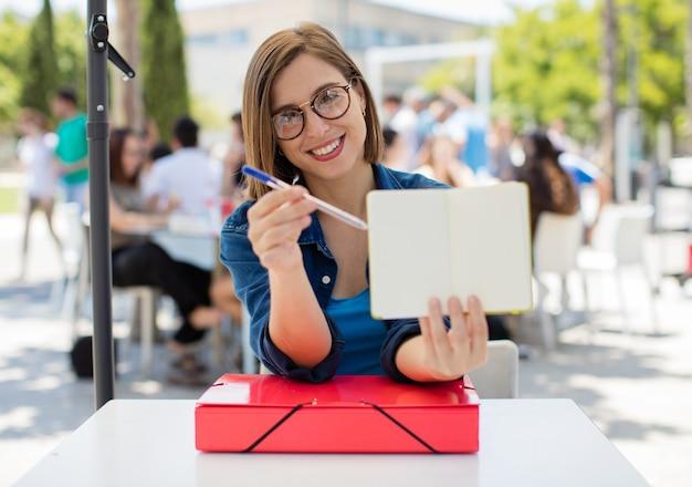 Jeune femme avec un cahier à l'université