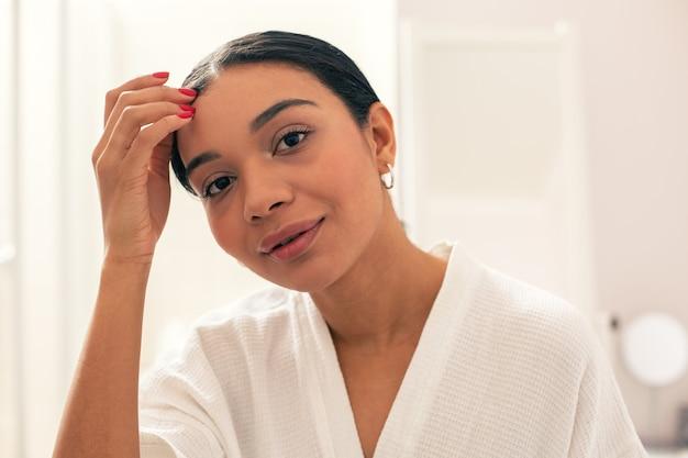 Jeune femme calme à l'air joyeuse et souriante tout en se tenant dans un peignoir blanc et en mettant une main sur sa tête