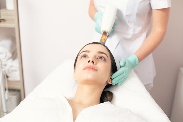 Jeune femme calme allongée sur le canapé médical pendant qu'un travailleur professionnel utilise un outil laser sur la tête