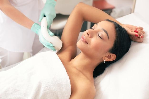 Jeune femme calme allongée les yeux fermés et mettant le bras levé tout en ayant une procédure d'épilation au laser dessus