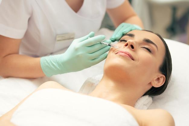 Jeune femme calme allongée les yeux fermés et souriante pendant qu'un cosmétologue professionnel fait une injection de vitamines