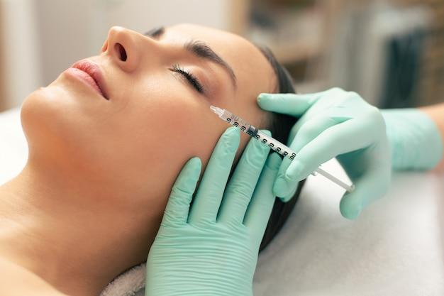 Jeune femme calme ayant les yeux fermés et main d'esthéticienne faisant une injection d'acide hyaluronique près de l'œil