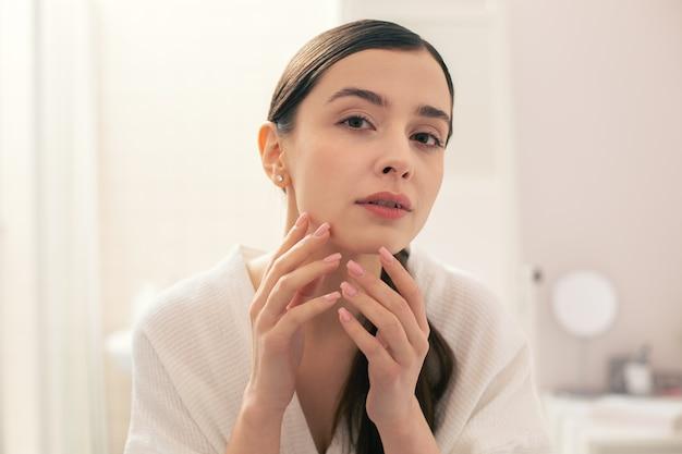 Jeune femme calme dans une serviette blanche à la recherche concentrée tout en touchant son menton et en regardant l'état de la peau