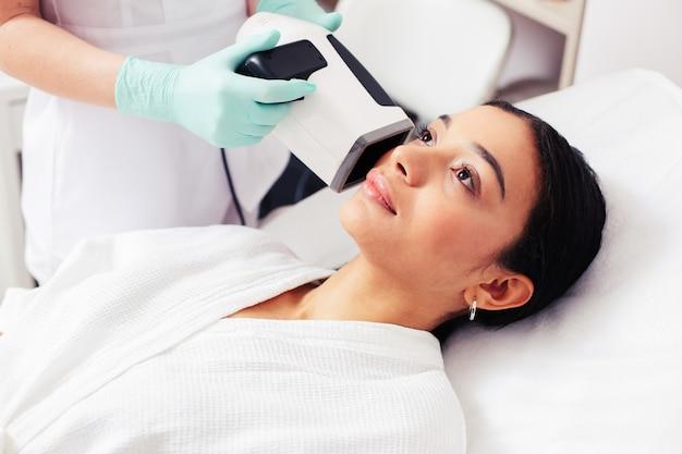 Jeune femme calme levant la main d'un cosmétologue tenant une caméra d'analyse de la peau près de sa joue
