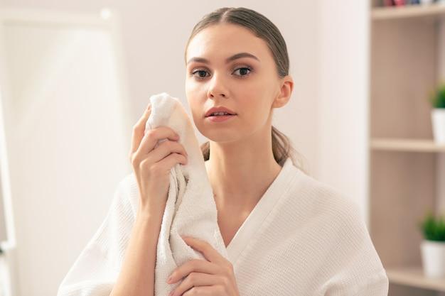 Jeune femme calme portant un peignoir blanc et l'air pensif en se tenant debout avec une serviette dans les mains