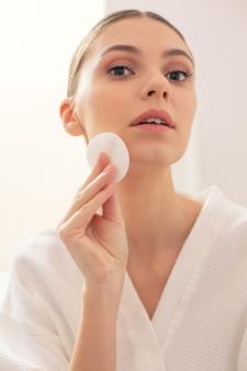 Une jeune femme calme et réfléchie, regardant attentivement tout en touchant la peau de sa joue avec un coton
