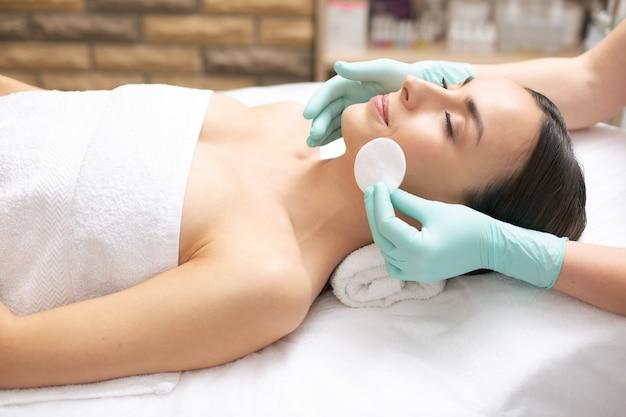 Jeune femme calme se relaxant lors de la procédure de nettoyage du visage et souriante pendant qu'un cosmétologue professionnel tient un coton