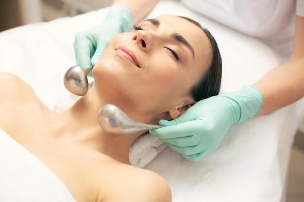 Jeune femme calme se sentant détendue pendant la procédure avec des bâtons cryogéniques