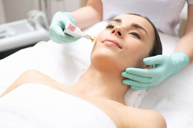 Une jeune femme calme souriante tandis qu'un dermatologue professionnel utilise l'ascenseur à oxygène frais sur son visage