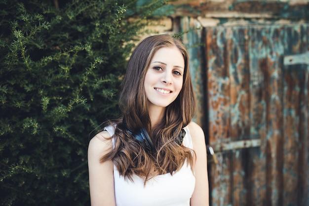 Jeune femme à la campagne avec des écouteurs à l'extérieur, souriant