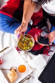 La jeune femme sur le canapé et avec du thé à la sauge sur la main.