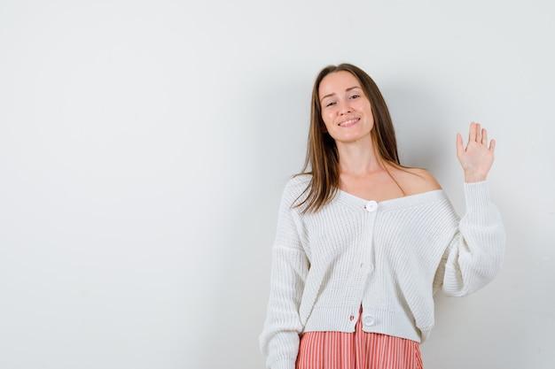 Jeune femme en cardigan et jupe en agitant la main pour salutation à heureux isolé