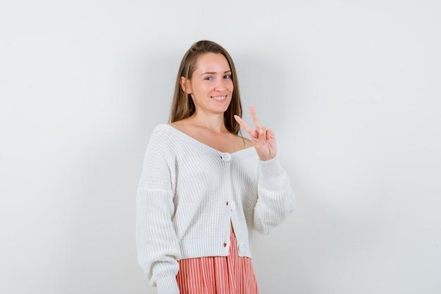 Jeune femme en cardigan et jupe montrant le geste de la victoire à la chance isolé