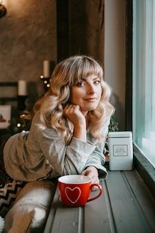 Jeune femme à carreaux avec une tasse de thé chaud dans un intérieur confortable de noël. le concept de préparation pour les vacances, faire un vœu et rêver
