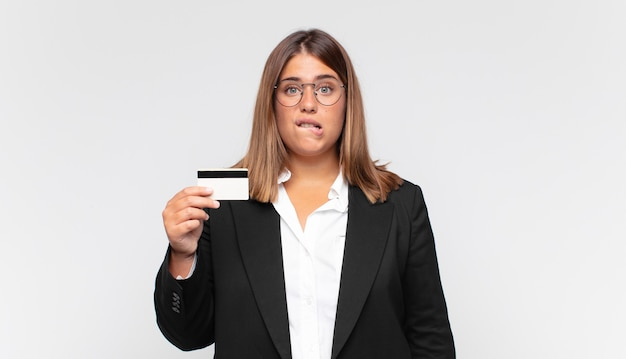 Jeune femme avec une carte de crédit à la perplexité et à la confusion, mordre la lèvre avec un geste nerveux, ne sachant pas la réponse au problème