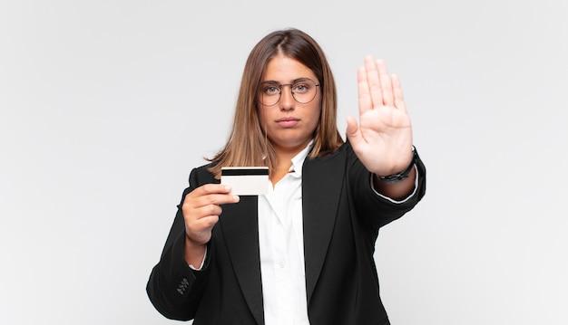 Jeune femme avec une carte de crédit à la recherche grave, sévère, mécontent et en colère montrant la paume ouverte faisant le geste d'arrêt