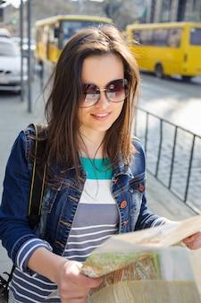 Jeune femme avec carte dans le vieux centre-ville