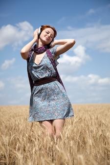Jeune femme avec un casque au champ de blé.