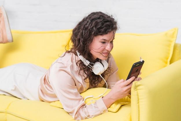 Jeune femme avec un casque autour du cou, couché sur un canapé jaune à l'aide de smartphone