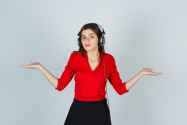 Jeune femme avec un casque d'écoute de la musique tout en faisant le geste des échelles en chemisier rouge